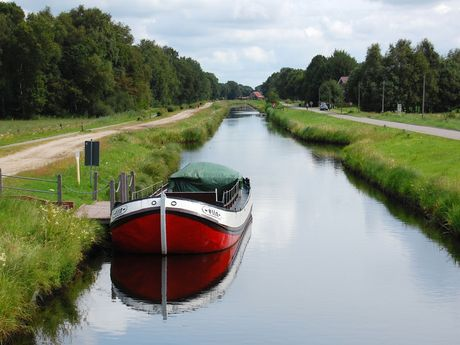 Ein Fehnkanal zieht sich mit grünen Ufern durch Uplengen