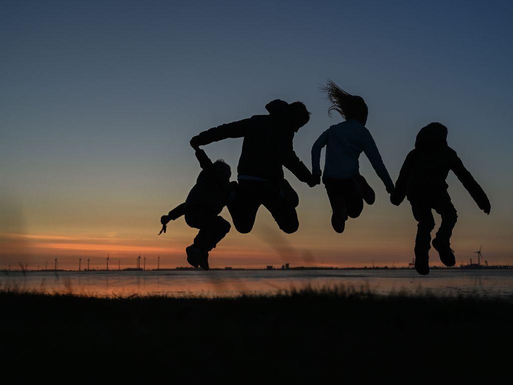 Familie springt Hand in Hand bei einem Sonnenuntergang in Ditzum, Südliches Ostfriesland