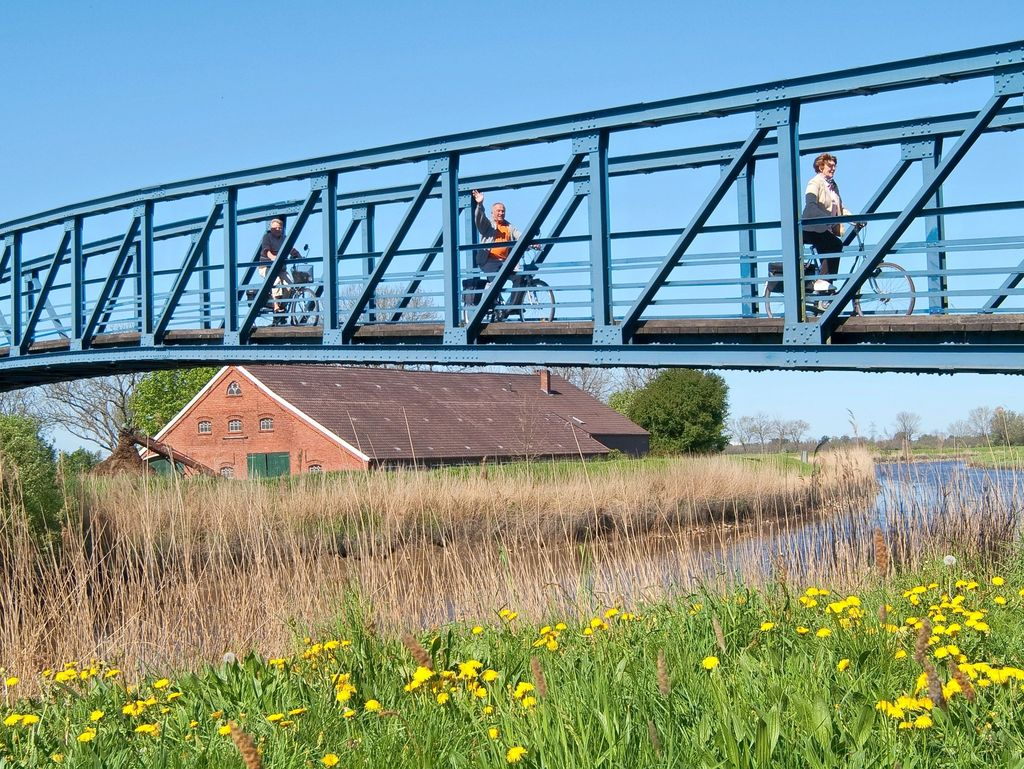 Fahrradfahrer auf der schmalsten Autobrücke Deutschlands in Amdorf, südliches Ostfriesland.