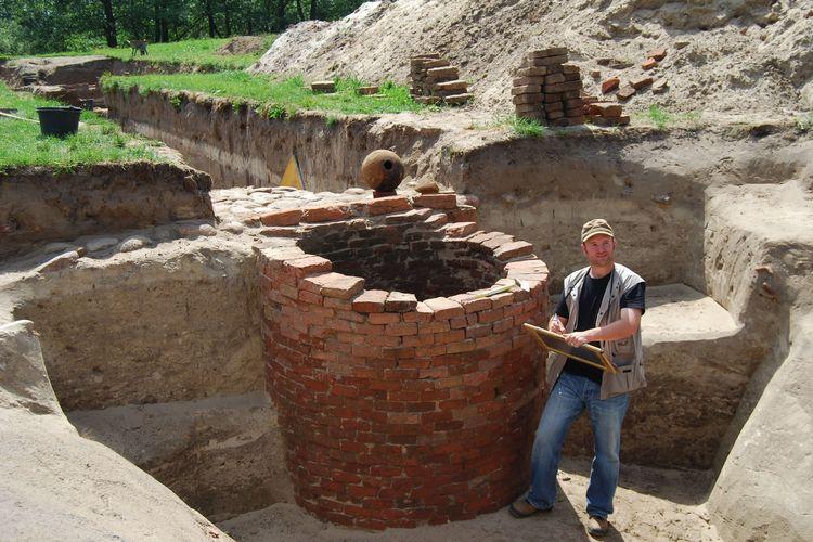 Entdecke Mauer einer Festung, ein Herr steht daneben und präsentiert das gefundene, Südliches Ostfriesland.