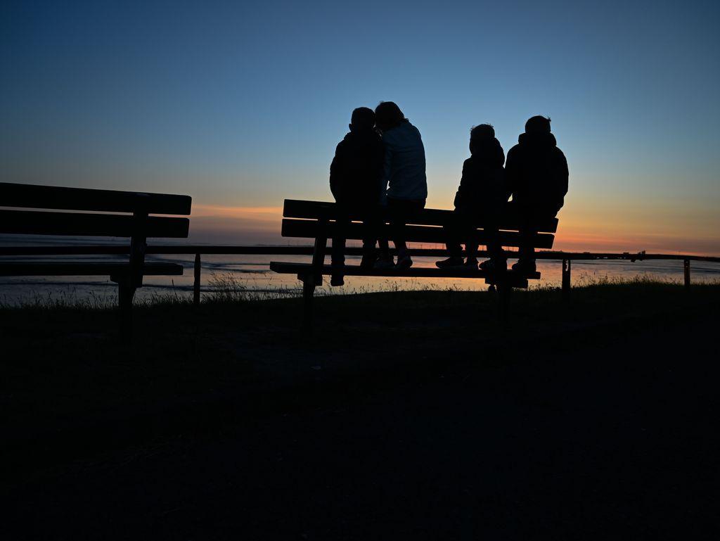Menschen sitzen auf einer Bank und schauen den Sonnenuntergang zu in Ditzum, Südliches Ostfriesland