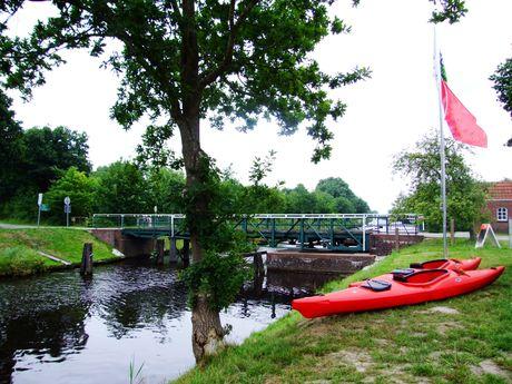 Rote Kanus an der Paddel- und Pedalstation am Ufer des Kanals in Oldersum