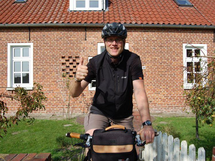 Radfahrer mit Helm vor einem Haus
