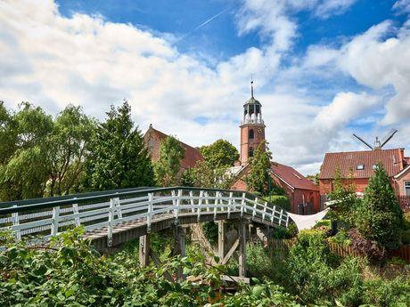 Brücke führt zum Ortskern der Gemeinde Ditzum und Kirche, Südliches Ostfriesland